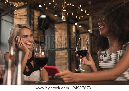 Amusing Stories. Cheerful Young Women Sitting At The Bar Counter, Drinking Wine And Laughing Heartil