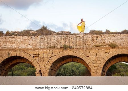Young And Attractive Caucasian Pregnant Woman In A Long Yellow Dress Dancing On The Top Of The Ancie