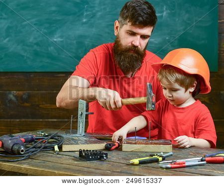 Father with beard teaching little son to use tools, hammering, chalkboard on background. Fatherhood concept. Boy, child busy in protective helmet learning to use hammer with dad. poster