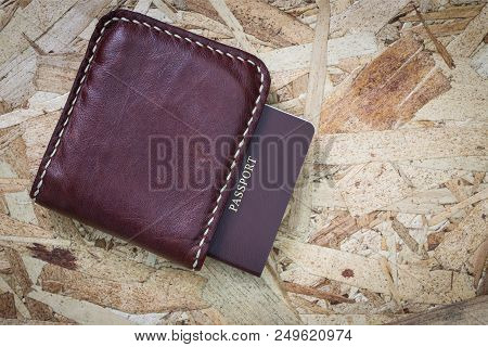 Top View Vintage Leather Wallet And Passport On Wooden Background