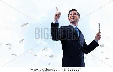 Cheerful and young businessman in black suit gesturing and smiling while standing with paintbrush in his hand against cloudy skyscape with flying paper planes view on background. poster