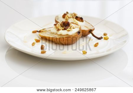 Backed Pear With Ricotta, Raisins And Honey On White Plate
