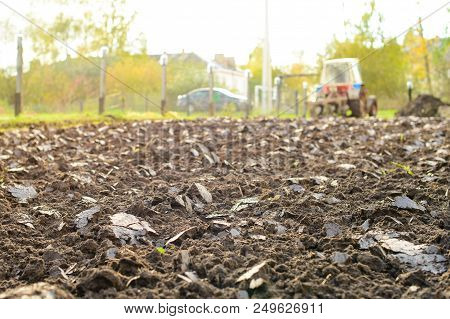 Tractor Plowing A Land, Rural Life In Russia. Selective Focus On Plowed Land. Concept Of Agriculture