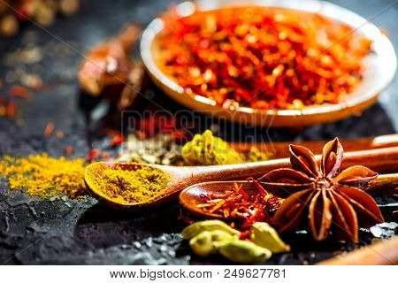 Spices. Various Indian Spices on black stone table. Spice and herbs on slate background. Assortment of Seasonings, condiments. Cooking ingredients, flavor