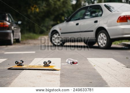 Skateboard And Child's Shoe On A Pedestrian Lines After Dangerous Traffic Incident