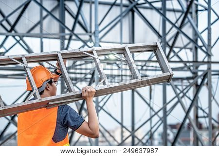 Young Asian Maintenance Worker With Orange Safety Helmet And Vest Carrying Aluminium Step Ladder At