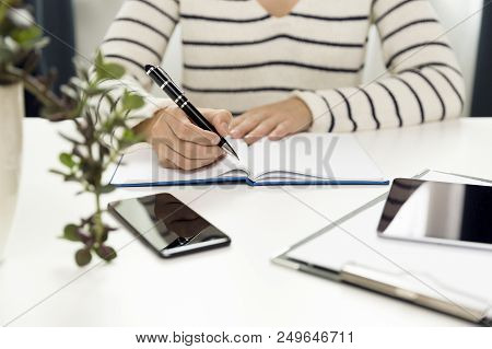 Young Business Woman Sitting At Table And Writing In Notebook. On Table Is Smartphone, And Tablet. F