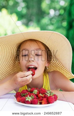 Portrait Of Cute Teen Girl In Big Hat Is Eating Strawberry At Summer Day