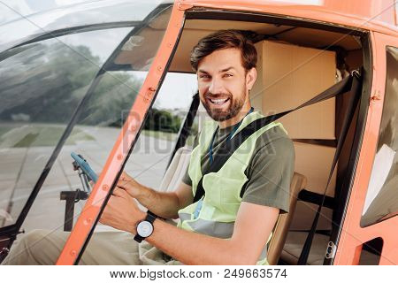 Help In Air. Jovial Male Volunteer Seating In Helicopter And Laughing To Camera