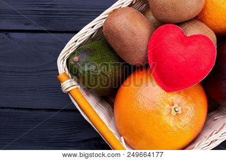 Fresh fruits in basket, top view. Variety of exotic fruits and felt heart. Healthy and nutritious diet. poster