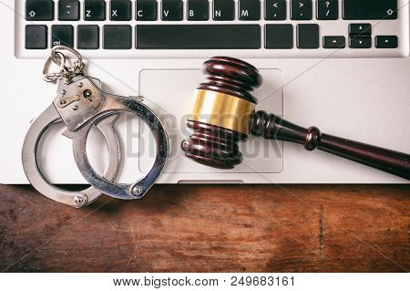 Cybercrime And Law Concept. Handcuffs And A Judge Gavel On A Computer On A Wooden Background, Copy S
