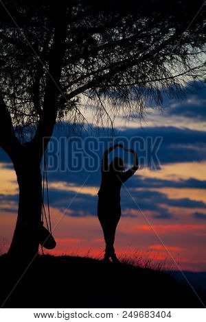 Beautiful sunset with woman standing and contemplating nature