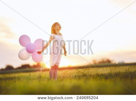 Happy kid is having fun on nature in the summer. Child is laughing and playing on meadow at sunset background. Girl with air balloons.