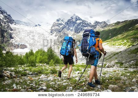 Two Hikers With Large Backpacks In Mountains. Tourists Hike On Rocky Mounts. Leisure Activity On Mou