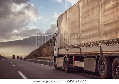 Truck On The Road In A Rural Landscape At Sunset.. Logistics Transportation And Cargo Freight Transp