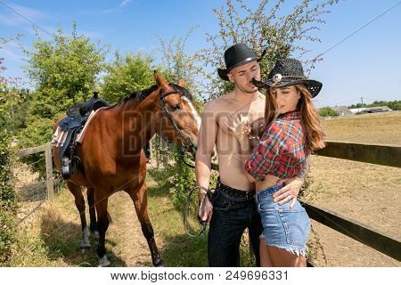 Cowboy And Cowgirl Couple With Horse And Saddle Argue With Ranch In Background