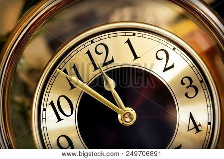 Golden clock face.  Hands showing five minutes to midnight.