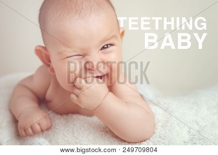 Small Cute Funny Baby Infant Teething With Face Expression Hands And Fingers In Mouth Sore Gums Soot