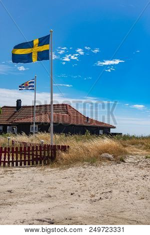 Swedish Flag Outside A Coast House. Picturesque Beach Landscape. Stock Photo.