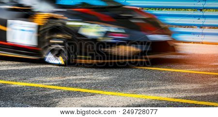 Motor Sport Car Racing On Asphalt Road With Blue Fence And Yellow Line Traffic Sign. Car With Fast S