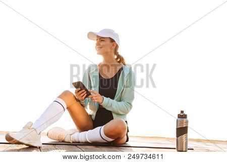 Image of strong young sports woman outoors on the beach looking aside using mobile phone.