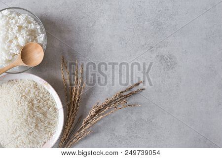 Raw Jasmine Rice With Stream Rice In Bowl And Seed On Concrete Ground