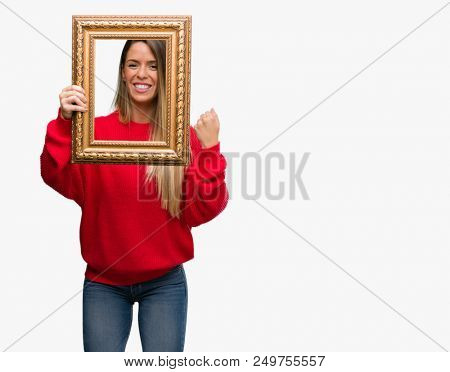 Beautiful young woman holding vintage frame screaming proud and celebrating victory and success very excited, cheering emotion