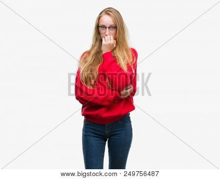 Blonde teenager woman wearing red sweater looking stressed and nervous with hands on mouth biting nails. Anxiety problem.