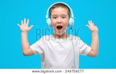 Dark haired little child listening music with headphones very happy and excited, winner expression celebrating victory screaming with big smile and raised hands