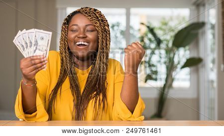 African american woman holding dollars screaming proud and celebrating victory and success very excited, cheering emotion