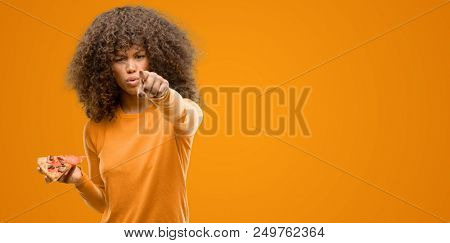 African american woman with a pizza slice pointing with finger to the camera and to you, hand sign, positive and confident gesture from the front