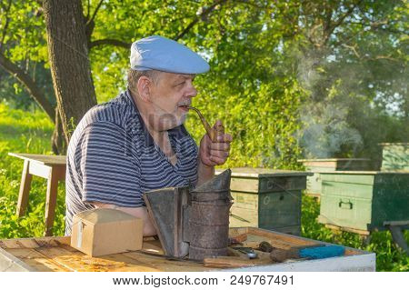 Outdoor Portrait Of Elderly Bee-keeper With Tobacco Pipe
