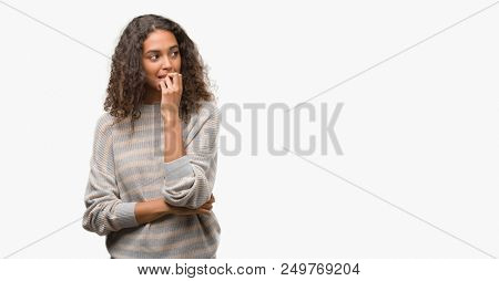 Beautiful young hispanic woman wearing stripes sweater looking stressed and nervous with hands on mouth biting nails. Anxiety problem.
