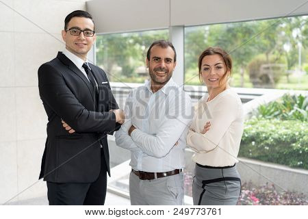 Corporate Portrait Of Three Members Of Successful Business Team. Joyful Business Partners Standing W