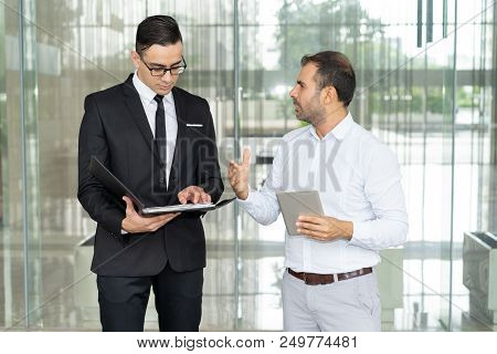 Emotional Businessman With Tablet Computer Proving His Point To Coworker. Financial Manager Reading