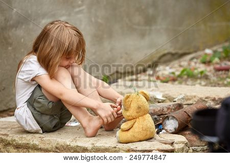 Orphan With Bare Feet And Dirty Face In A Shabby Clothes Playing With Used Teddy Bear On The Street.