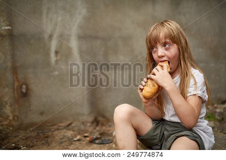 Poor Hungry Homeless Girl Eating A Piece Of Bread In The Dirty Alley, Selective Focus. Poverty And P