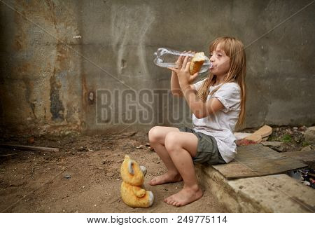 Poor Thirsty Homeless Girl Drinking Water From Plastic Bottle In The Dirty Alley, Selective Focus. P