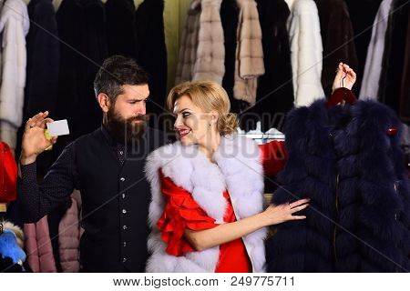 Couple In Love Shops In Fur Mall. Girl With Smiling Face Wearing White Mink Fur. Couple Shopping Con