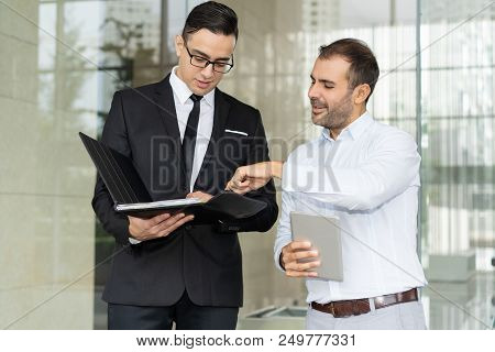 Smiling Entrepreneurs Discussing Business Document In Folder. Attorney Showing Important Document To