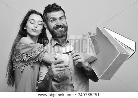 Man With Beard Holds Credit Card And Money Box. Guy With Beard And Lady With Smiling Faces Do Shoppi