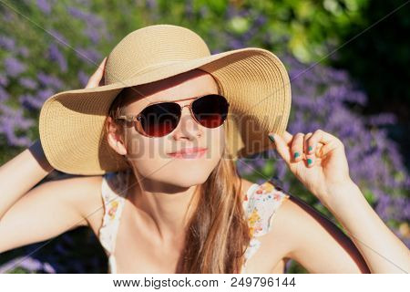 Summertime Lavender. Young Happy Woman With Floppy Hat Sitting In Lavender Field.