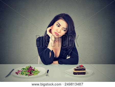 Young Woman Sitting At Table With Salad And Cake Craving For Dessert And Having Diet Dilemma On Gray