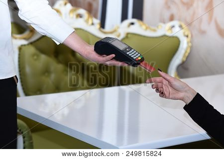 Credit Card Payment And Electronic Bank Concept. Customer Puts Credit Card Into Machine. Cashiers Ha