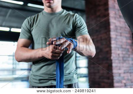 Strong sportsman. Strong muscle sportsman wearing khaki shirt holding professional blue wrist wraps poster