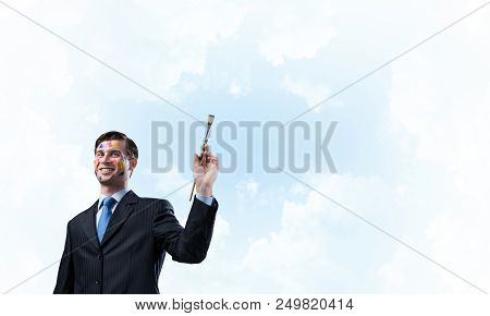 Happy and young businessman in black suit holding paintbrush in his hand and smiling while standing against blue cloudy skyscape view on background. poster