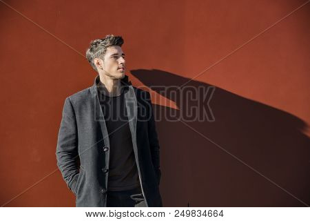 Serious Young Handsome Man In Winter Outfit Leaning On A Red Metal Wall While Looking To A Side Of T