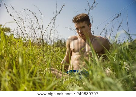 Handsome Muscular Shirtless Young Hunk Man Outdoor In Nature Sitting On Grass. Showing Healthy Muscl