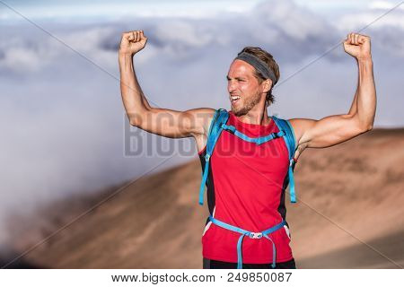 Fitness achievement fit athlete man screaming with fists up in the air winner arms up. Success in sport hiker on summit of mountain - goal challenge.