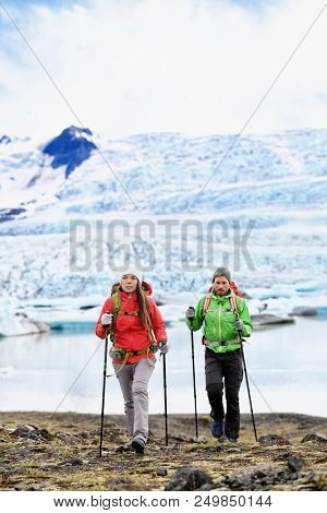 Winter hikers walking on ice glacier in Iceland. Tourists hiking in mountains in cold weather with hiking poles and trekking equipment. Travel lifestyle people on adventure.